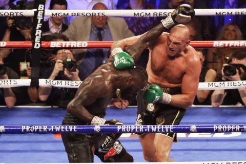 Tyson Fury, right, connects with a right hook against Deontay Wilder in the fifth round during ...