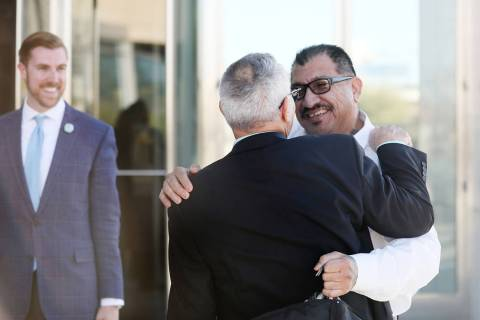Attorney Shawn Perez, hugs defendant Pastor Palafox outside the Lloyd D. George U.S. Courthouse ...