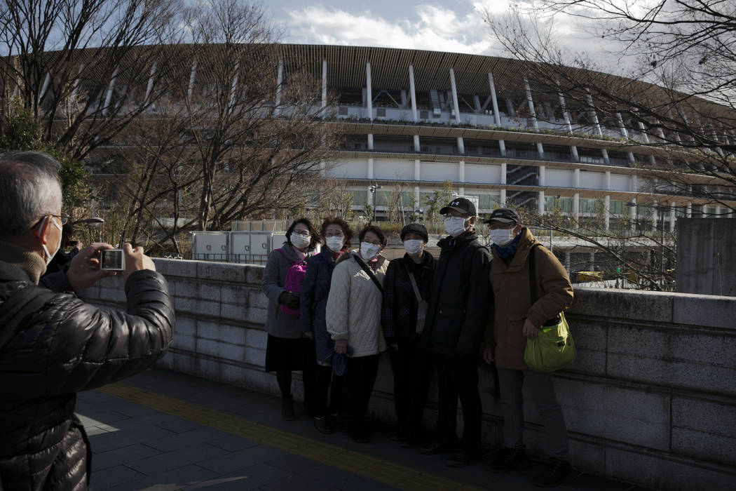 Tourists wear masks as they pause for photos with the New National Stadium, a venue for the ope ...