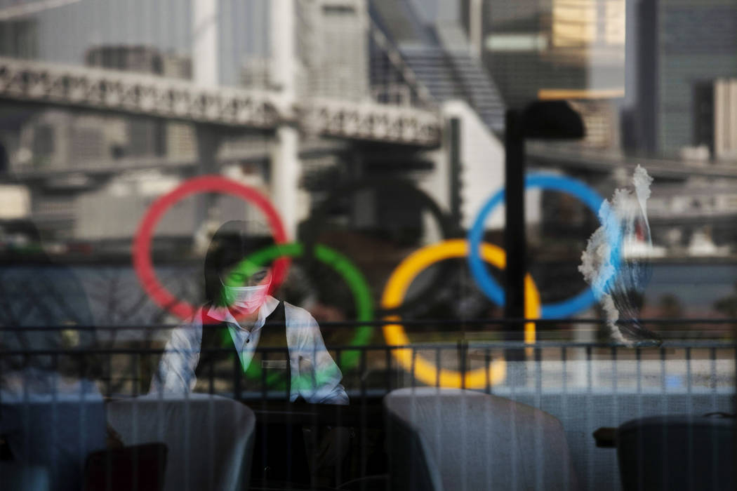 The Olympics rings are reflected on the window of a hotel restaurant as a server with a mask se ...