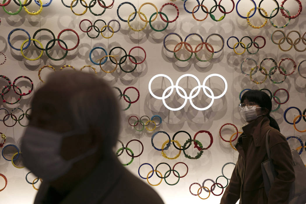 Two people wear masks as they visit the newly opened Japan Olympic Museum located near the New ...