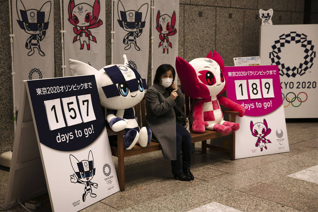 A woman removes her mask before taking pictures with the mascots of the Tokyo 2020 Olympics and ...