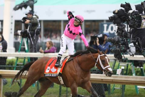 Luis Saez rides Maximum Security, and celebrates after crossing the finish line first during th ...