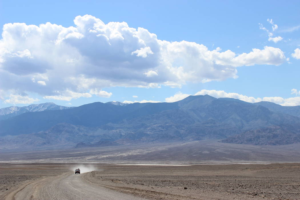 A vehicle travels along West Side Road, located at the base of the Panamint Mountains in Death ...