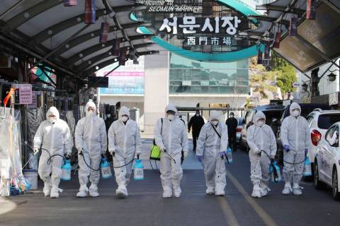 Workers wearing protective gears spray disinfectant as a precaution against the COVID-19 at a l ...