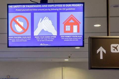A slide flashes on a screen reminding passengers to wash hands often at the McCarran Internatio ...