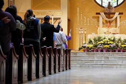The Rev. Gerald Grupczynski, pastor of Our Lady of Las Vegas Roman Catholic Church, right, hold ...