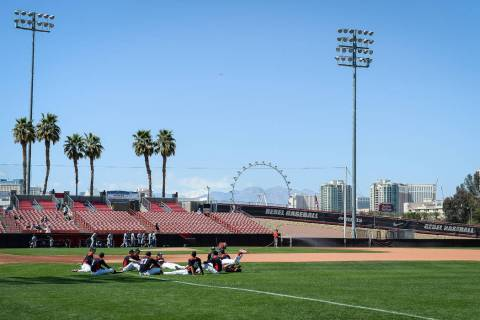 UNLV sits on the field while warming up before a game against UNR during an NCAA baseball game ...