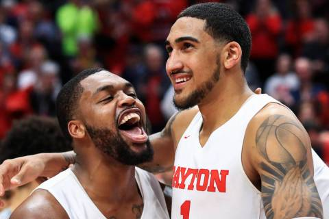 Dayton's Trey Landers, left, reacts with Obi Toppin, middle, as he celebrates scoring his 1,000 ...