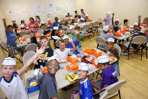 Kids enjoy a free meal sponsored by Three Square June 29, 2010, at the Summer Food Service Prog ...
