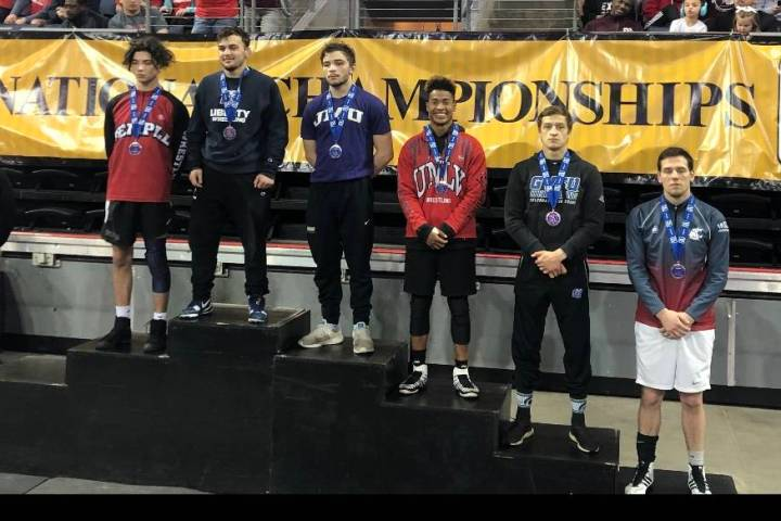 Michael Canada, third from the right, is seen on the podium following a wrestling match. (UNLV ...
