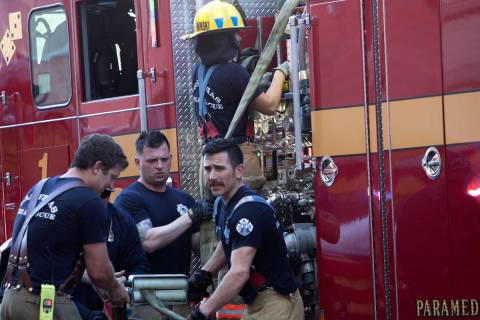 Las Vegas firefighters roll up their fire hose after putting out a structure fire at 320 S. 1st ...