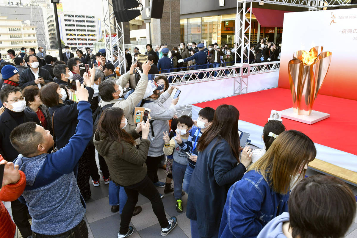 People gather to take a look at Olympic flame on display in Sendai, Miyagi prefecture, north of ...
