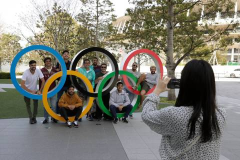 A group of students from Uruguay pose for a souvenir picture on the Olympic Rings set outside t ...