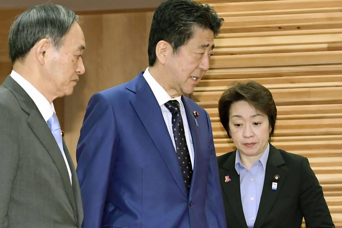 Japanese Prime Minister Shinzo Abe, center, walks past Olympic Minister Seiko Hashimoto, right, ...