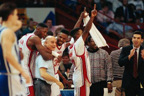 UNLV coach Jerry Tarkanian is hugged by players as the final seconds of the Final Four tick tow ...