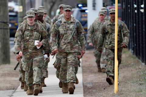 National Guard personnel march in formation as they leave duty after working Thursday, March 19 ...