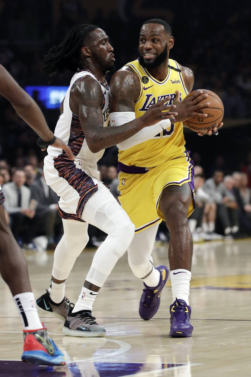 Los Angeles Lakers' LeBron James, right, is defended by Brooklyn Nets' Taurean Prince during th ...