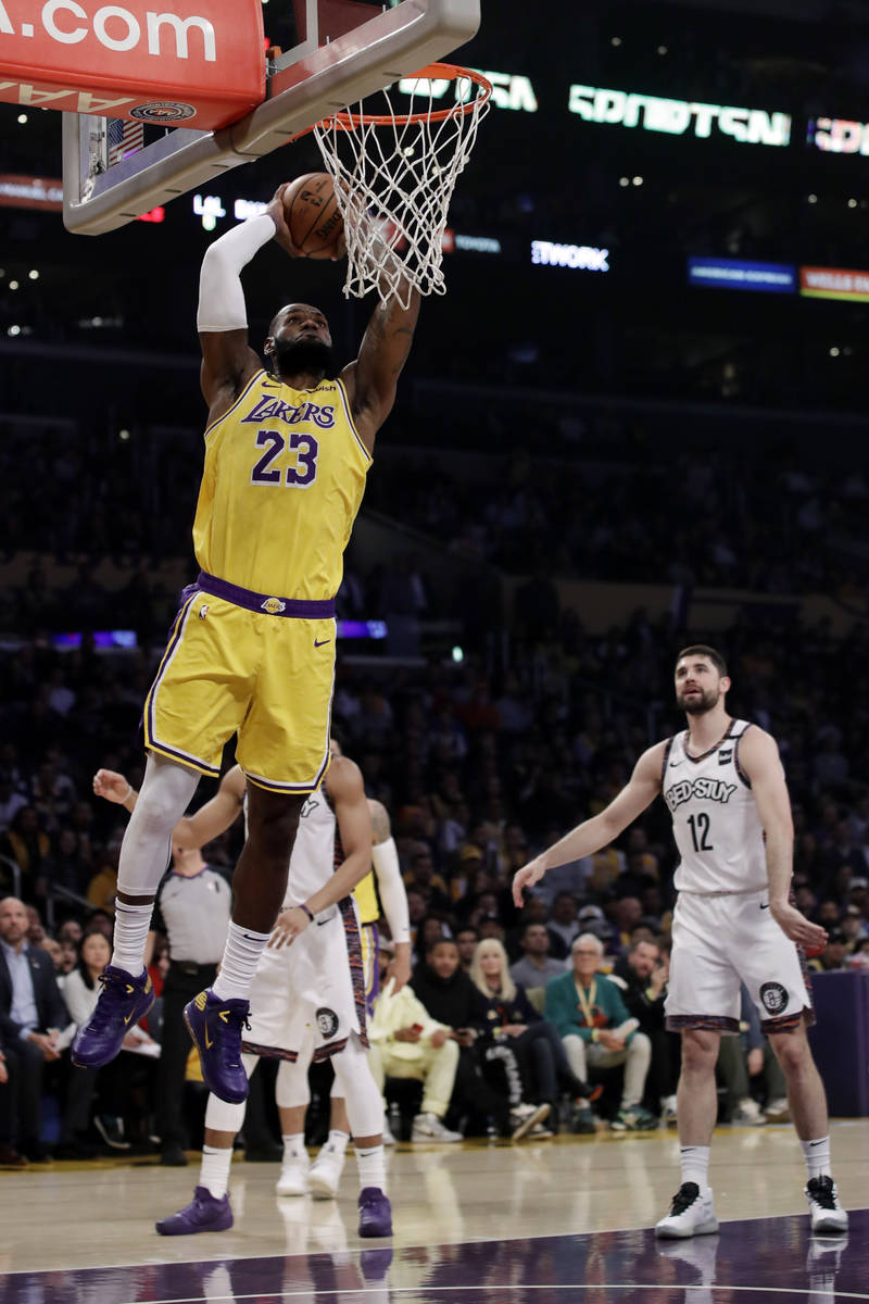 Los Angeles Lakers' LeBron James (23) dunks during the first half of an NBA basketball game aga ...