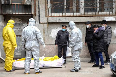 In this Feb. 1, 2020, file photo, funeral home workers remove the body of a person suspected to ...