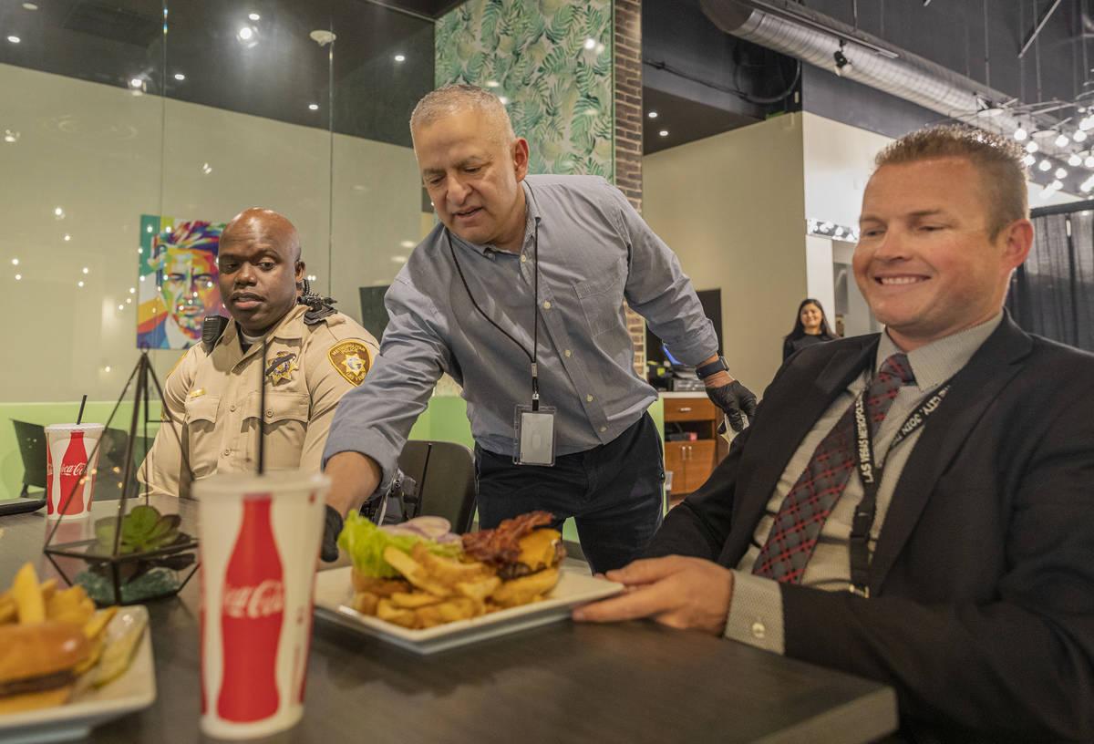 Food and beverage director Hank Serrano, center, serves Sgt. Albert Reeder, left, and Lt. Alan ...