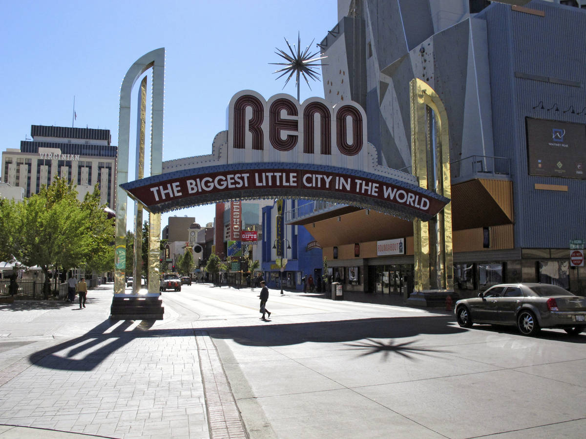In this Oct. 11, 2016, file photo, pedestrians pass beneath the Reno arch as traffic passes on ...