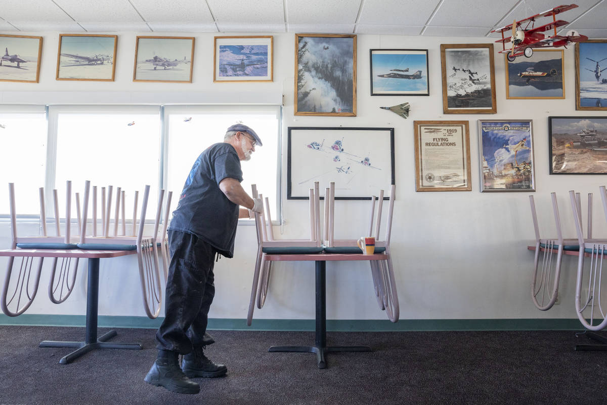 Sunshine & Tailwinds Cafe owner Stephen Maynard puts a sanitized chair up on the table at t ...