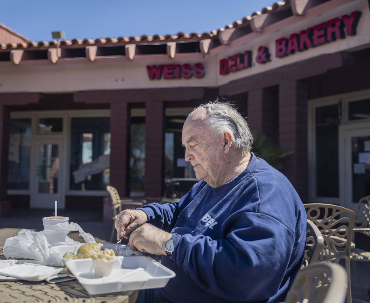 Forrest Darby, 76, long time customer of Weiss Deli and Bakery, eats his takeout order on the p ...