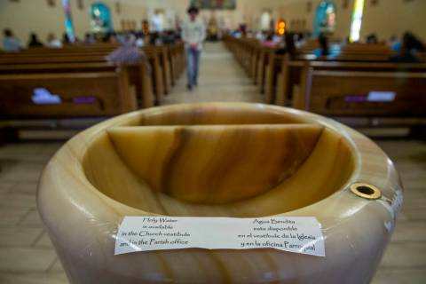 Notes in English and Spanish read that there is no holy water in the font currently for Sunday ...