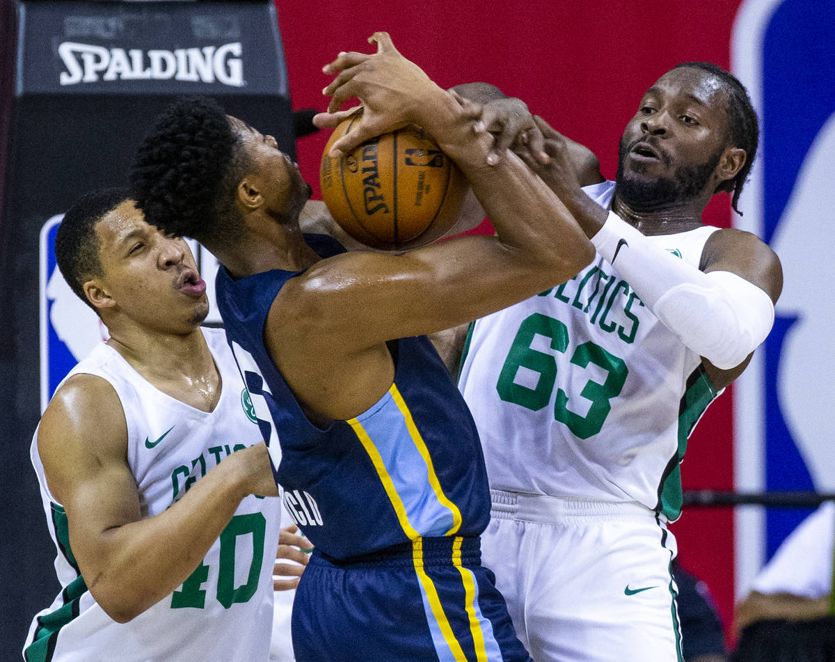 Memphis Grizzlies forward Bruno Caboclo, center, fights for a rebound with Boston Celtics cente ...