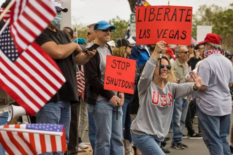 Protester Lauren Robison welcomes others arriving to the Re-Open Nevada protest at the Grant S ...