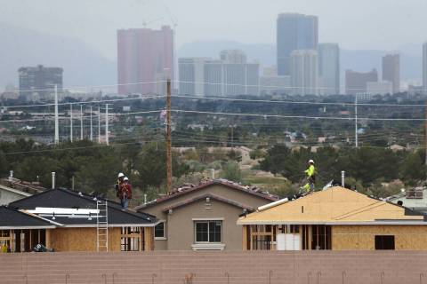 Construction workers install the roof of new homes near S Hollywood Boulevard and E Vegas Valle ...