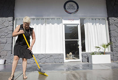 Megan Linney sweeps up the side walk in front of her downtown Las Vegas skin care salon, The La ...