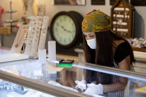 Brittany Bailey wears a mask and gloves during her first shift back after coronavirus-caused no ...