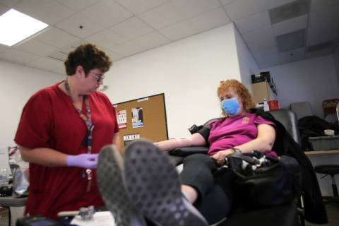 Phlebotomist Eva Clappa, left, takes a blood donation from Susan Edwards during a blood drive s ...