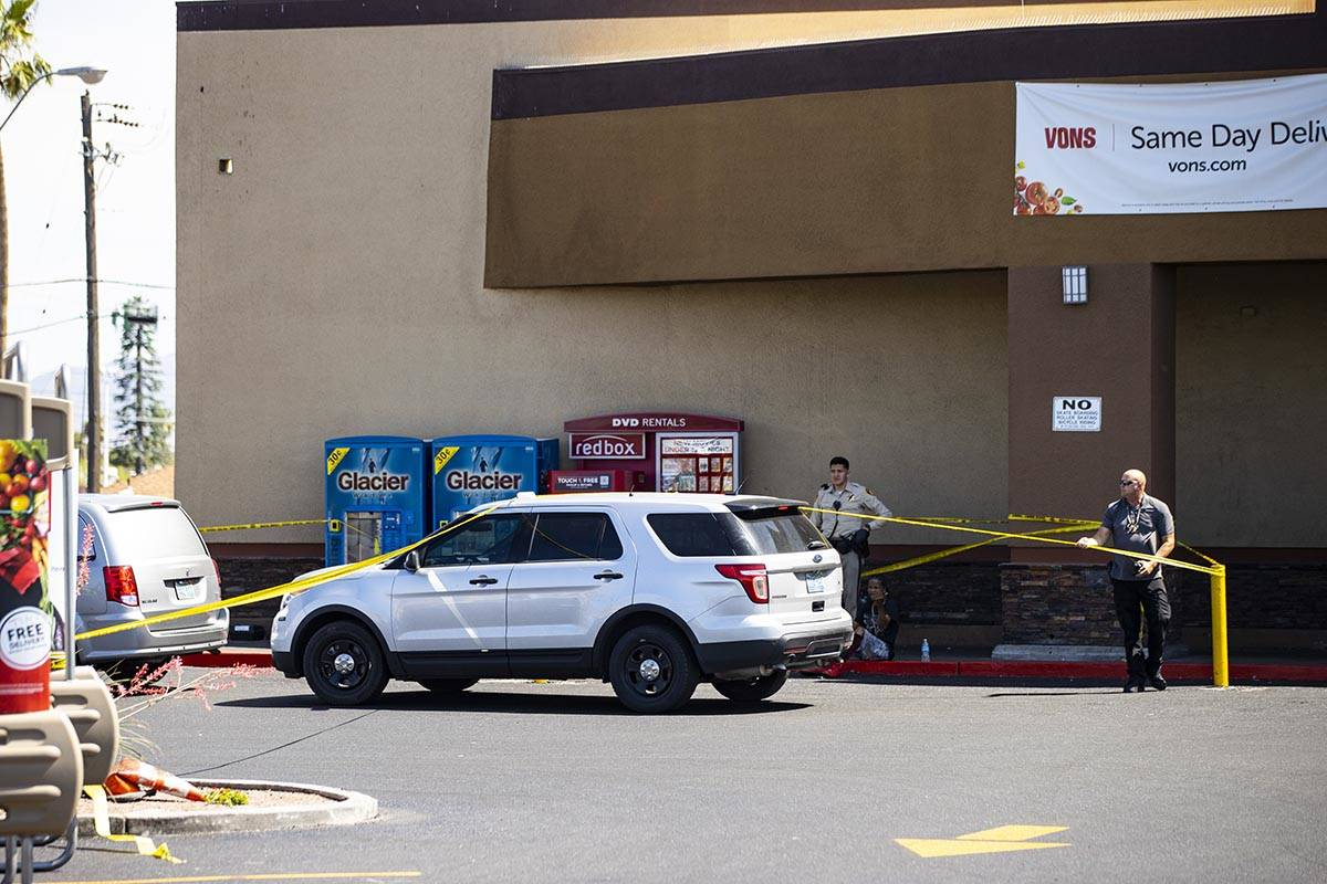 A man is detained as Las Vegas police investigate the scene of a shooting at Tropicana Avenue a ...