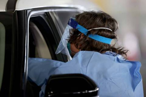 Registered nurse Megan Ryan works at the COVID-19 testing facility in the parking garage at The ...