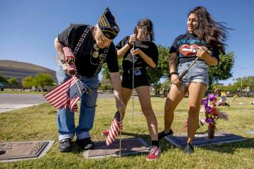 Army veteran Howard Greenspon, left, plants another American flag on a veteran's grave with the ...