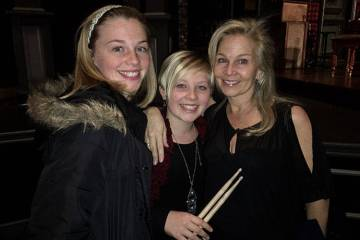 The Belk family, from left, Andress, Eliza and Megan, with drumsticks once used by their late f ...