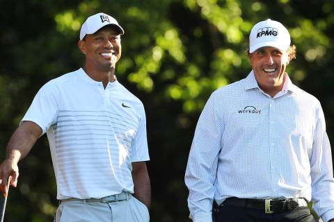 FILE - In this April 3, 2018, file photo, Tiger Woods, left, and Phil Mickelson share a laugh o ...