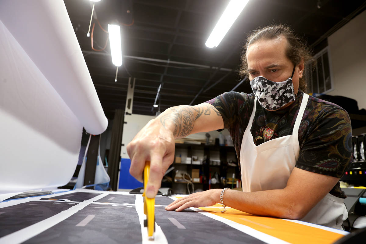 Former chef Jean Paul Labadie, creator of ApronTie, cuts fabric to make his product for chefs a ...