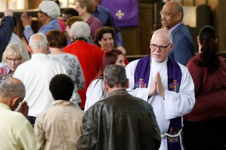 The Rev. J. Barry Vaughn, right, exchanges the sign of peace during a Mass celebrated at Christ ...