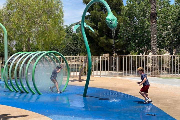 Children running through sprinklers at Aliante Nature Discovery Park's splash pad as it reopene ...