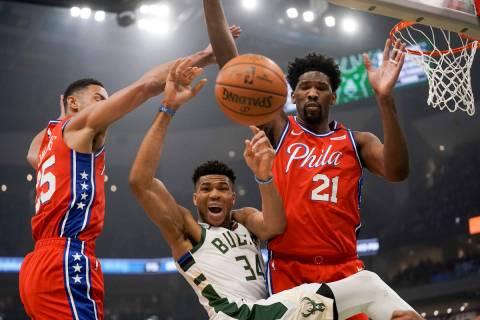 Milwaukee Bucks' Giannis Antetokounmpo is fouled as he drives between Philadelphia 76ers' Ben S ...