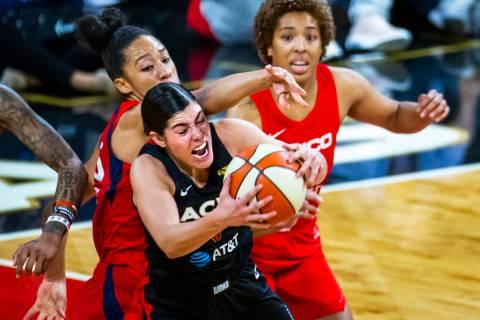 Las Vegas Aces guard Kelsey Plum (10, center) secures a loose ball over Washington Mystics forw ...