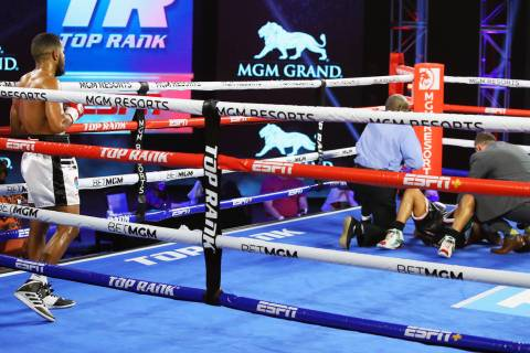 Jessie Magdaleno is attended to after taking a low blow from Yenifel Vicente in the fourth roun ...