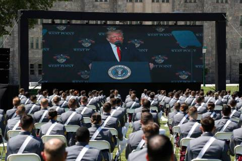 A screen displays President Donald Trump as he speaks to over 1,110 cadets in the Class of 2020 ...