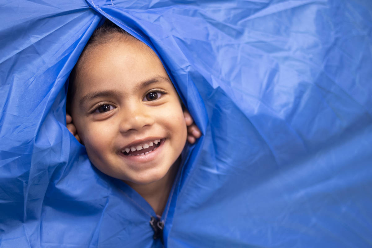 "Paisley peeks through the tent, which is in one of the preschool rooms for ""camping week,& ..."