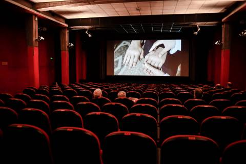 People sit in a cinema in Milan, Italy, Monday, June 15, 2020. Movie theaters are reopening acr ...