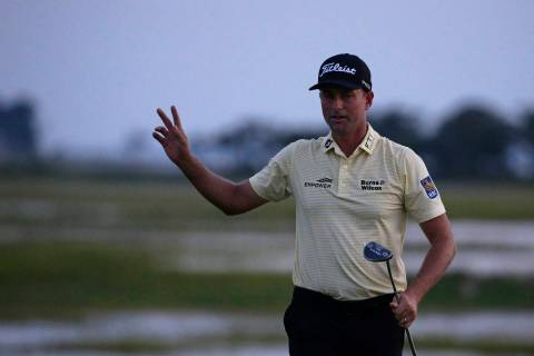 Webb Simpson waves as the sun disappears on the 18th green, on a course with no fans due to the ...